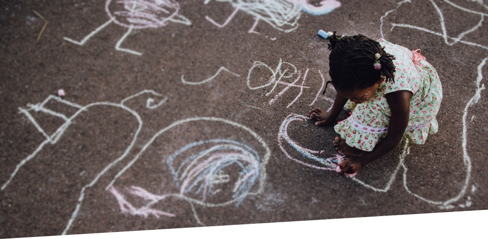Young girl drawing in chalk on the sidewalk.
